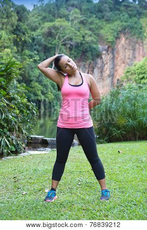 sporty woman stretching side of neck after exercise in outdoor park