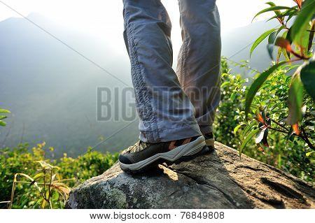 woman hiker stand on mountain peak rock