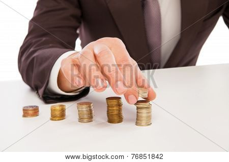 closeup shot of hands counting coins over white