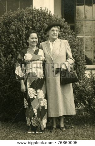CANADA - CIRCA 1940s: An antique photo shows  portrait of a Two women: Asian and Caucasian