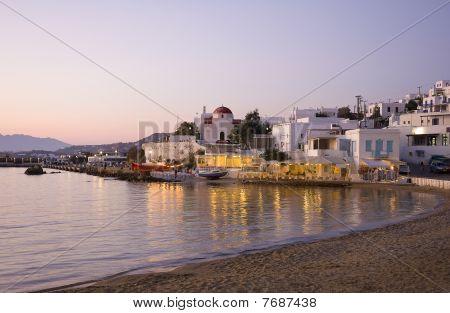 Sonnenuntergang auf Mykonos Island ein Gebäude, eine Kirche und ein Restaurant am Meer