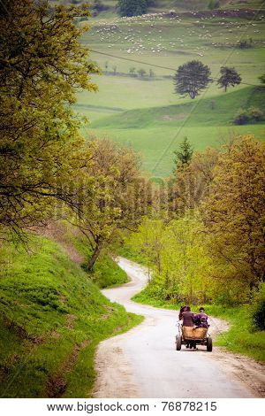three Farmers on old wooden cart on their way in Transylvania Romania