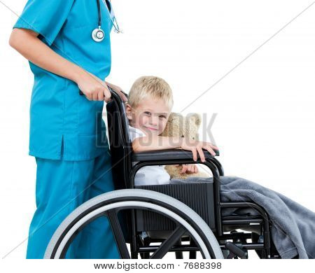 Bright Female Doctor Carrying Adorable Little Boy With His Teddy Bear In The Wheelchair