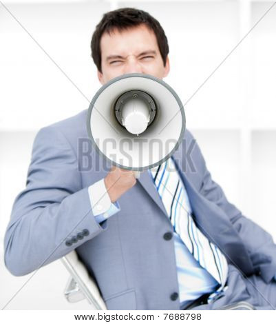 Furious Young Businessman Yelling Through A Megaphone