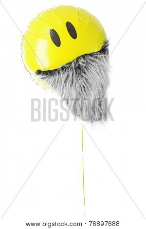 A yellow mylar balloon with two eyes and a furry gray beard.  On a white background.
