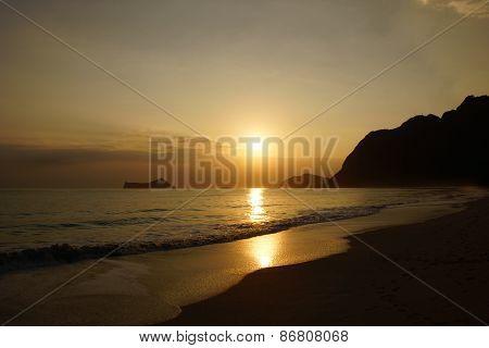 Early Morning Sunrise On Waimanalo Beach Over Rock Island Bursting Through The Clouds