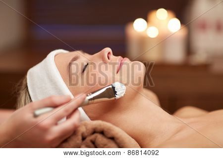 people, beauty, spa, cosmetology and skincare concept - close up of beautiful young woman lying with closed eyes and cosmetologist applying facial mask by brush in spa poster