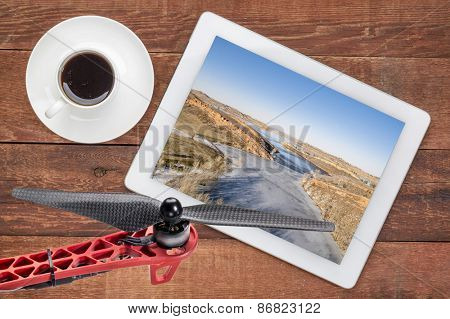 aerial landscape photography concept - reviewing aerial pictures of  Horsetooth Reservoir in Colorado on a digital tablet with a drone rotor in foreground. Screen picture copyright by the photographer