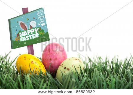 Easter egg hunt sign against small easter eggs nestled in the grass