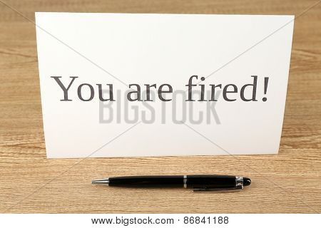 Message You're Fired with pen on wooden background