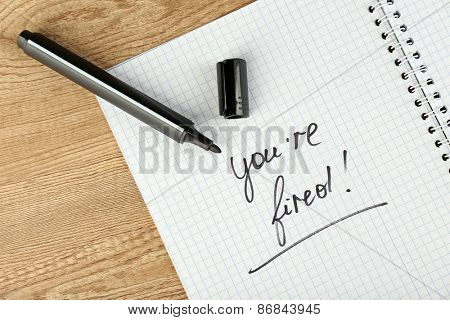 Message You're Fired on notebook with marker on wooden table, closeup