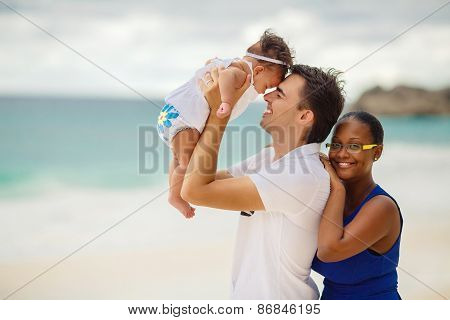A young interracial family with a child on the beach.