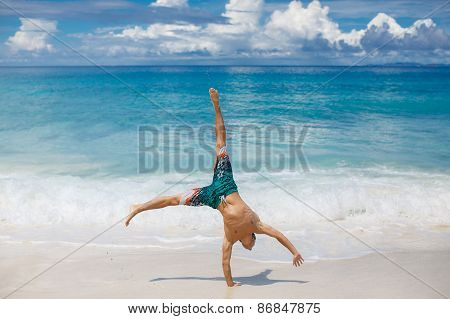 A young man performs acrobatics on the beach.