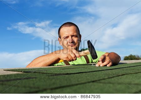 Man Finishing Installing The Bitumen Roof Shingles