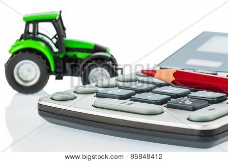 a tractor and a red pen lying on a calculator. cost of gasoline, wear and insurance. costs and subsidies in agriculture poster