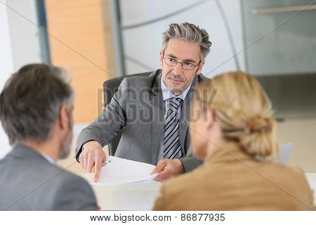 Mature couple signing contract in lawyer's office poster