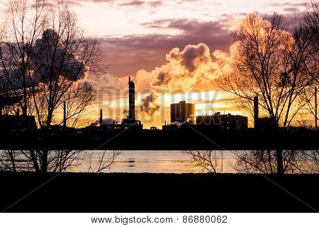 Factory with smokestacks at sunset