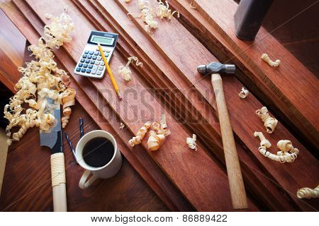 Wood working or carpentry scene with coffee. High quality hard wood lumber and wood working tools and coffee on a work bench.