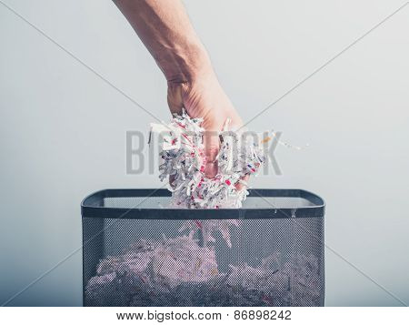Hand Putting Shredded Paper In Basket