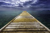 An empty dock leading out of the blue tropical water on Mustique island. poster