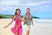 Happy couple having fun running on Hawaii beach vacations in Hawaiian clothing wearing Aloha shirt and pink sarong sun dress and flower leis for traditional wedding or honeymoon concept. poster