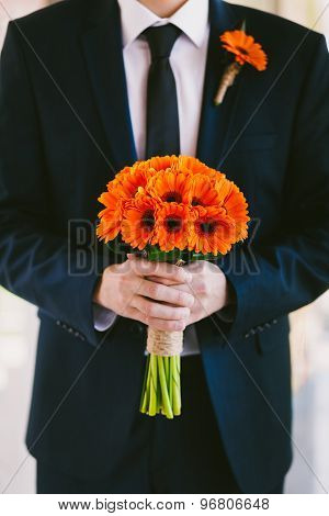 Groom In Blue Suit Holding Wedding Bouquet Of Flowers In Hands