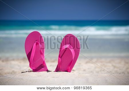 Pink Flip Flops On Sandy Beach Near Sea. Summer Vacation Concept