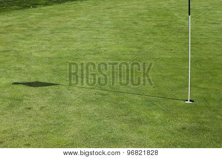 Flagstick Hole On A Putting Green In A Golf Course.