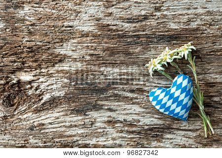 Fabric heart with edelweiss flowers on weathered wood background