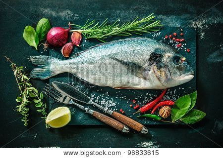 Fresh Gilt-head bream with spices and seasoning on slate plate poster