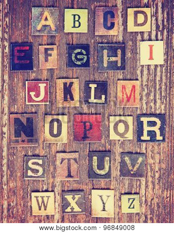 a complete set of cardboard blocks of the english alphabet on a wooden background toned with a retro vintage instagram filter effect app or action