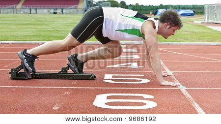 Handsome Sprinter On The Starting Line Putting His Foot In The Starting Block