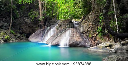 Beautiful nature background. Waterfall flows through tropical rainforest and falls into natural pond