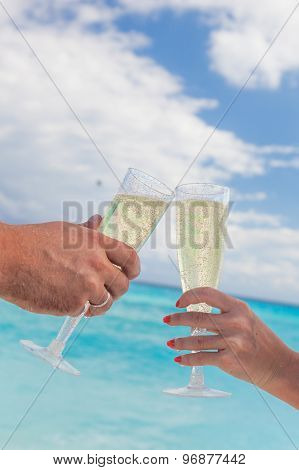 Clanging Glasses With Champagne At Sandy Beach