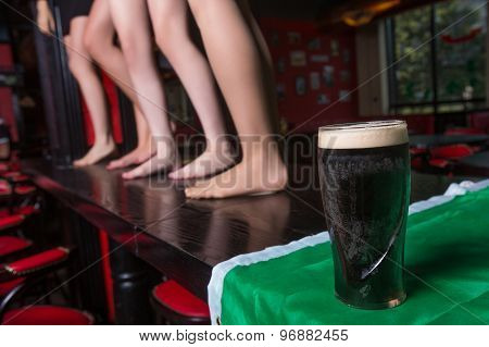 mug with a dark beer at the bar. background of women's feet