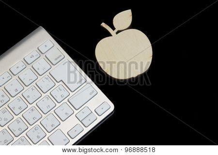 Wireless Keyboard And Wooden  Apple Sli?e Isolated On Black Glass
