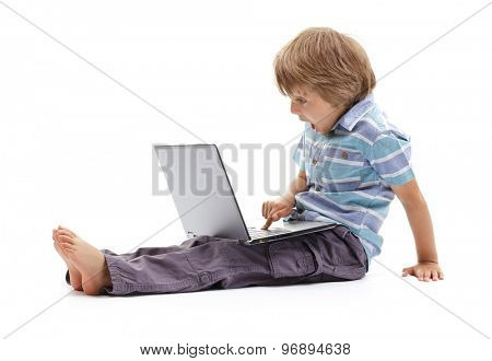 Surprised expression on a boys face whilst getting into mischief on a laptop computer concept for child internet safety, social media or education and homework