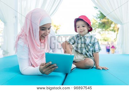 Happy Muslim young woman and little boy on summer vacation