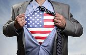 Businessman in classic superhero pose tearing his shirt open to reveal t shirt with the American flag concept for patriotism, freedom and national pride poster