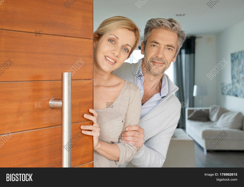 opening front door. Couple Opening House Front Door To Welcome People In F