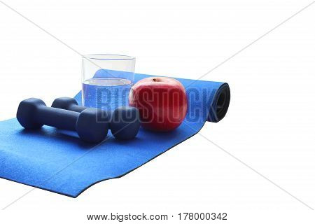 Close up of a pristine red apple two dumbbells  and glass water, blue atheletic small rug of  isolated on white with reflection , sound lifestyle
