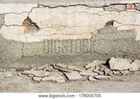 Close up of plaster textured background of obsolete demolished wall with ruins on the ground