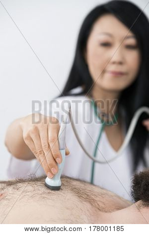 Doctor Placing Ultrasound Probe On Patient's Chest