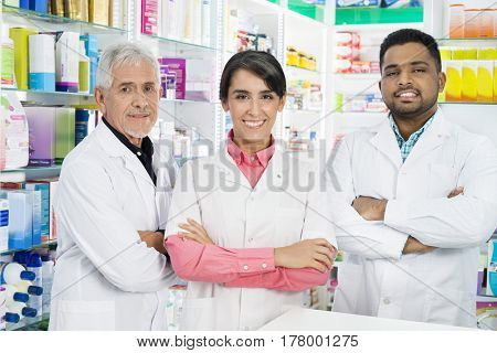Multiethnic Chemists Standing Arms Crossed In Pharmacy
