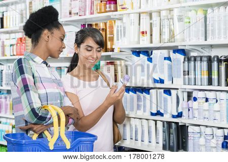 Female Friends Looking At Product In Pharmacy