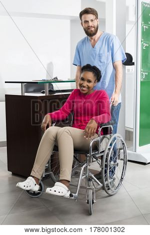 Smiling Patient Sitting In Wheelchair While Nurse Standing At Ho