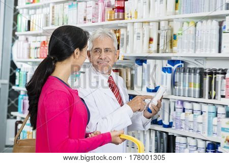 Chemist Looking At Customer While Pointing At Shampoo Bottle