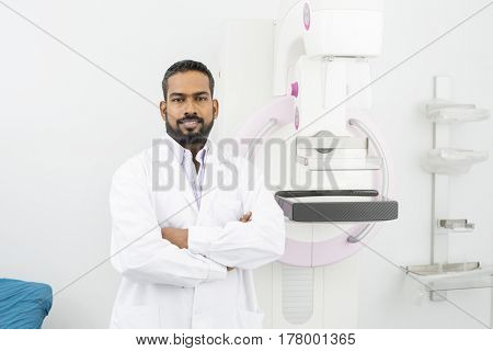 Confident Doctor Standing Arms Crossed By Mammography Machine