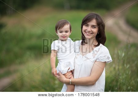 A happy emotional young mother in a white dress with a toddler daughter in her arms is walking in the clearing in the open air the concept of lifestyle is motherhood tenderness and love.