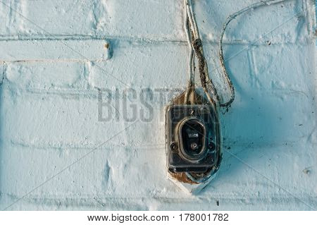 Close up of obsolete button doorbell on wall with spiderweb on it